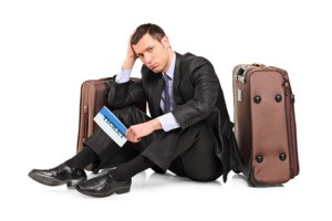 A sad business traveler seated next to a suitcase with a ticket in his hand isolated on white background